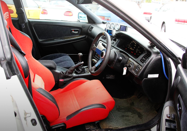 INTERIOR OF DRIVER'S BUCKET SEAT AND STEERING.