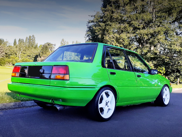 REAR EXTERIOR OF AE82 COROLLA SEDAN TO GREEN PAINT.