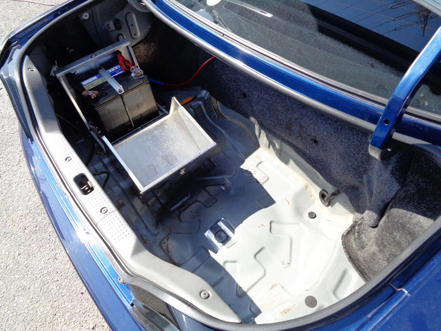 BATTERY RELOCATION INTO TRUNK ROOM.